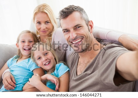 Man taking picture of wife and twins sitting on a couch in the living room - stock photo