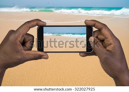 Man taking picture with mobile phone on a beach - stock photo