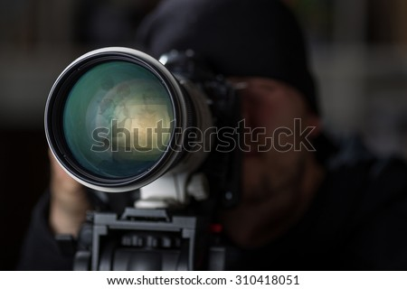 Man taking pictures of cheaters with a large telephoto lens - stock photo