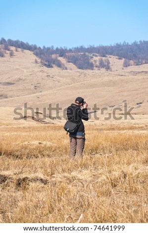 man taking pictures to landscape