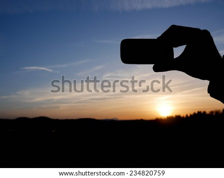 Man taking pictures with her smartphone at sunset - stock photo