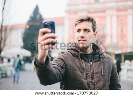 Man taking self portrait in the city with mobile phone - stock photo