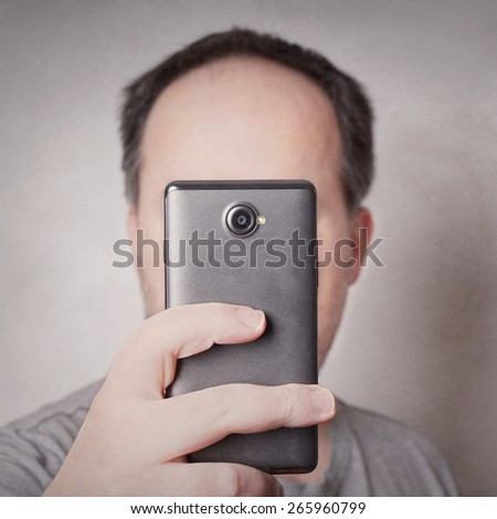 man taking selfie picture with smart phone camera looking like a cyclops with added filter     - stock photo
