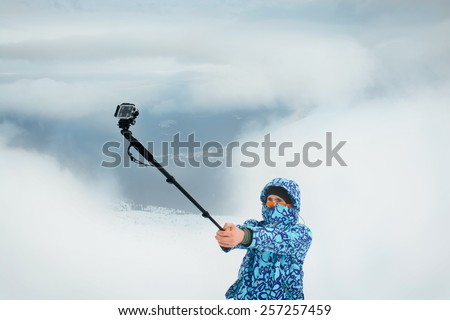 Man taking selfie using action camera at the mountains. Outdoor activities on fresh winter air - stock photo