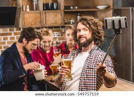 Man taking selfie with his friends durring home party