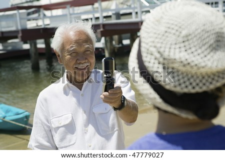 Man Taking Woman's Photograph with Camera Phone - stock photo
