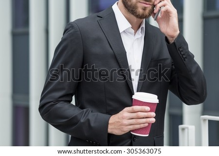Man talking by the phone with coffee in his hand - stock photo