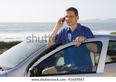 Man talking on cell phone beside a car at the sea - stock photo