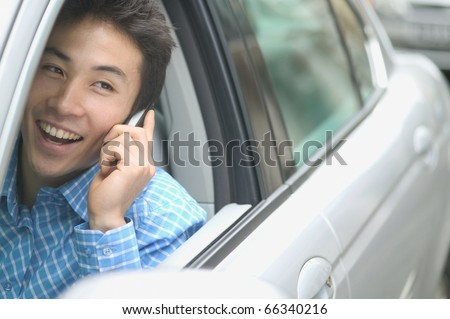 Man talking on cell phone in car - stock photo