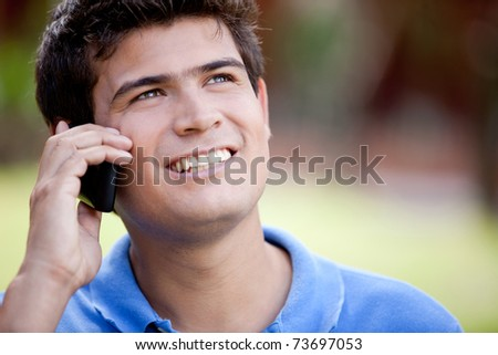 Man talking on his mobile phone outdoors - stock photo