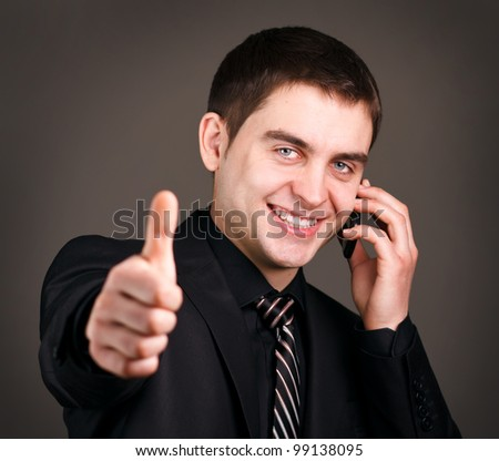 man talking on mobile phone showing thumb