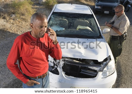Man talking on phone after car accident - stock photo