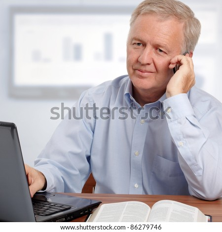 Man talking on phone and smiling in front of the laptop and the Bible - stock photo