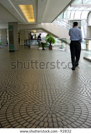 Man talking on phone in an outdoor mall. - stock photo