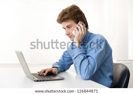 Man talking on phone in front of the laptop