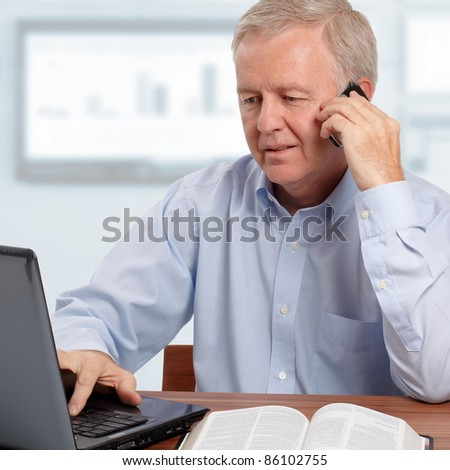 Man talking on phone in front of the laptop and the Bible - stock photo