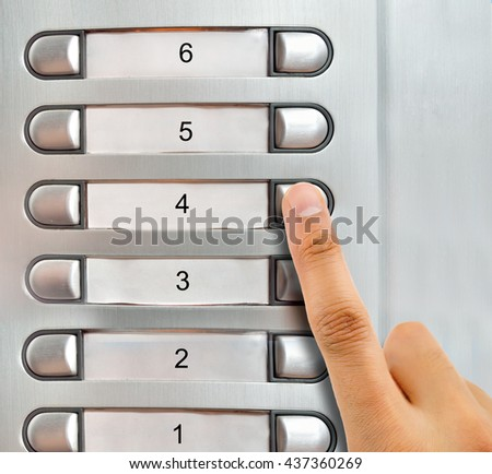 man talking on the intercom and presses the button - stock photo