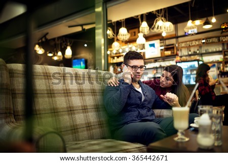 Man talking on the phone hearing bad news while his girlfriend consoling him. - stock photo