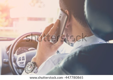 Man talking on the phone while driving his car ,vintage tone - stock photo