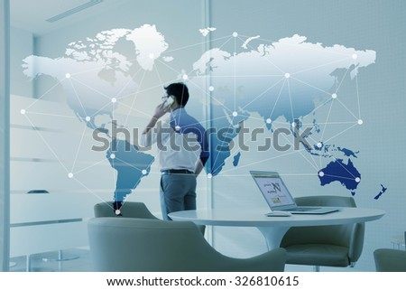 Man talking via mobile phone and laptop with globalization layer effect - stock photo