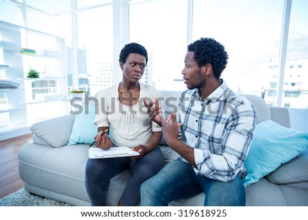 Man talking with pregnant wife while writing on notepad at home