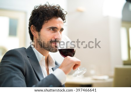 Man tasting a glass of red wine in a restaurant - stock photo