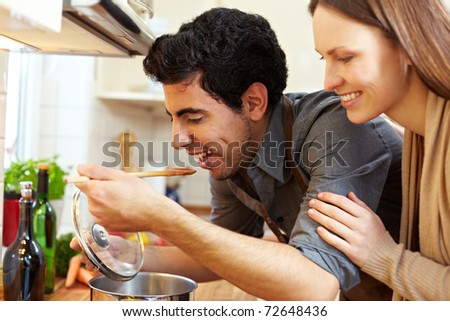Man tasting soup on a stove in kitchen while happy woman is watching - stock photo