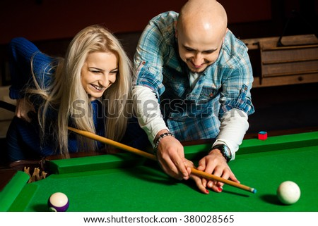 Man teaches his girlfriend how to play on the pool table. Billiard sport concept. American pool billiard. Pool billiard game. - stock photo