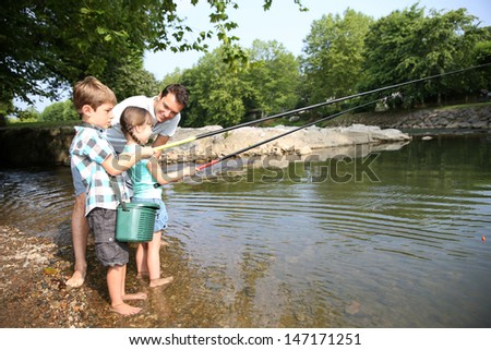 Man teaching kids how to fish in river - stock photo
