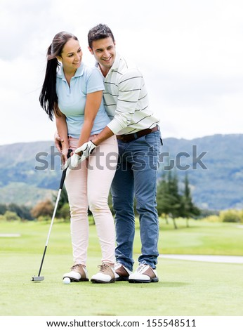 Man teaching woman how to play golf at the course  - stock photo