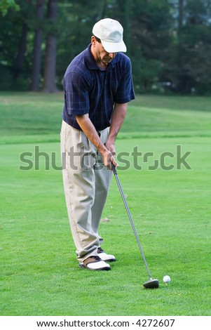 Man teeing  up to hit a big drive onto the fairway. - stock photo