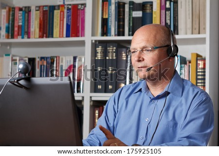Man telephoning with computer, headset and webcam, copy space - stock photo