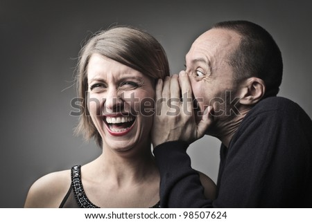 Man telling a laughing woman a joke