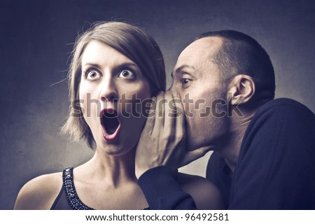 Man telling an astonished woman some secrets - stock photo