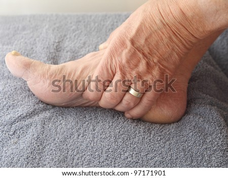 man tends to his aching arch - stock photo