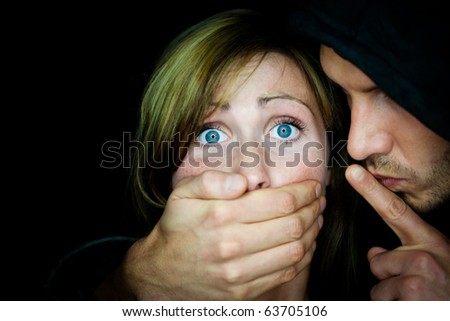 Man terrifying female holding mouth to make her silent - stock photo