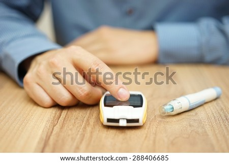 man testing glucose level with a digital glucometer, diabetes treatment - stock photo
