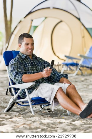 Man text messaging on cell phone at campsite - stock photo
