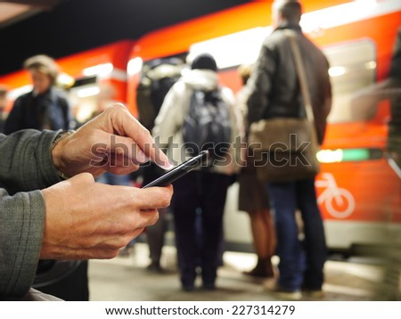 Man texting on his mobile in a Berlin station with a train drawn up at the platform and commuter waiting to board, selective focus to the mans hand and phone - stock photo