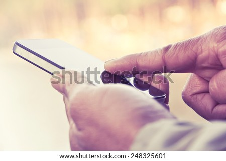Man texting on his smartphone - stock photo