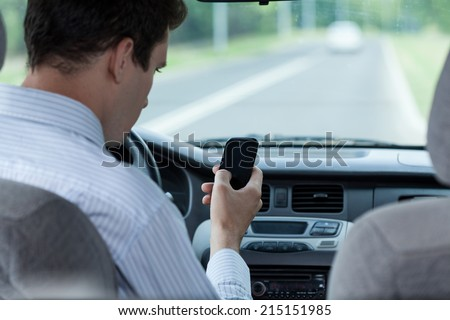 Man texting on mobile phone during driving a car, horizontal - stock photo
