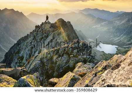 Man thinking and looking to the cloudy sky and calm summer sunset in mountains - stock photo