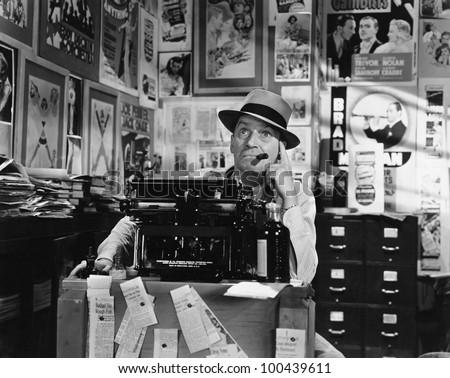 Man thinking at typewriter - stock photo