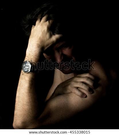 Man thinking problems worried dark - stock photo