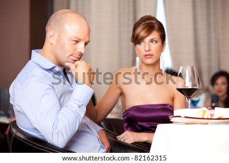 man thinking, sad woman at restaurant table - stock photo