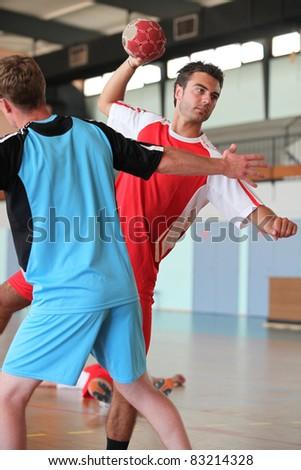 Man throwing ball during handball game - stock photo