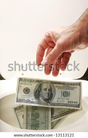 Man throwing US $100 bills into toilet - stock photo