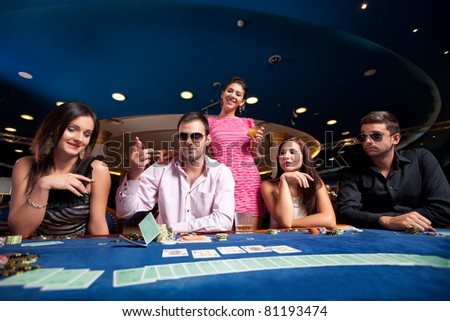 man throwing with his poker cards while other players watch him - stock photo