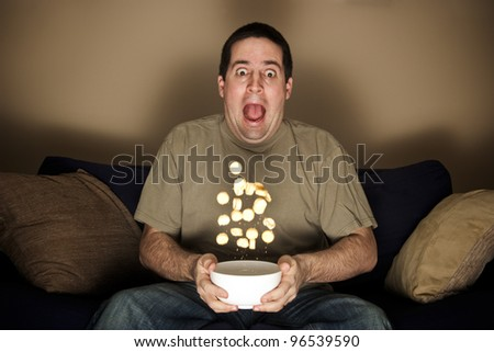 Man throws crisps frightened while watching horror movie - stock photo