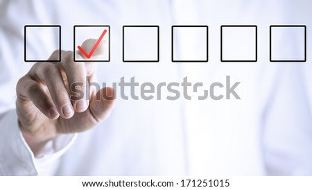 Man ticking a check box in a line of empty boxes on a virtual screen or interface with his finger - stock photo